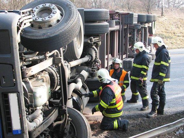 Hasiči z HZS Benešov prohlížejí u havarovaného kamionu nádrž s naftou