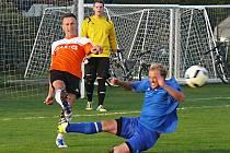 Bývalý ligový hráč a autor první branky Martin Müller odkopává v dresu Všenorského SK míč před skluzujícím nespeckým Michalem Párysem.