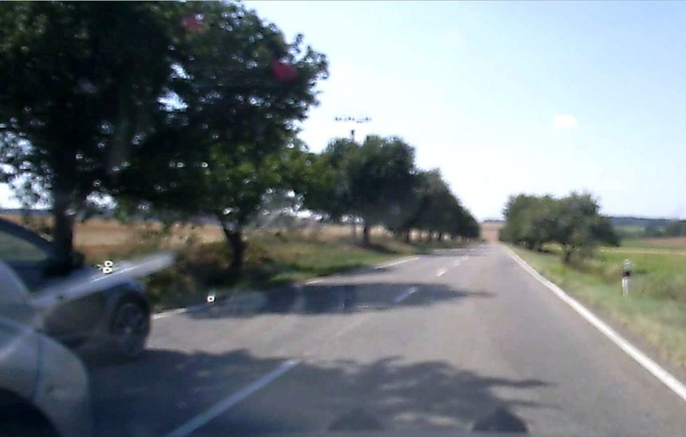 Na nezřetelném záběru z kamery je vidět vlevo část černošedého neznámého vozidla.