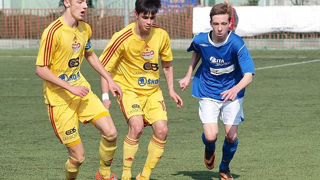 Benešovský Jakub Vosáhlo (v modrém) se snaží uniknout dvěma hráčům Dukly Praha Kozlovi a Micovi.