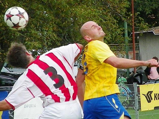 Kapitán Benešova, obránce Luboš Braný (ve žlutém), svedl hlavičkový souboj v hráčem Jiren.