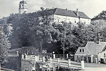 Palackého náměstí ve Vlašimi v roce 1942 sbývalým železným mostem. Na pravé straně dům čp.58 čalouníka Jana Hrdličky a vpravém rohu dům čp. 59 Karla a Jana Toulových, je vidět výklenek pro sošku.