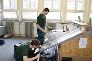 Úkolem bylo oplechovat maketu sedlové střechy s odvětraným hřebenem a dvěma prostupy.