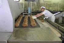 Pracovník pekáren dohlíží na hladký průběh závěrečné etapy výroby pečiva. Z tohoto stroje vyjíždí  každou hodinu tisíce kusů chleba.