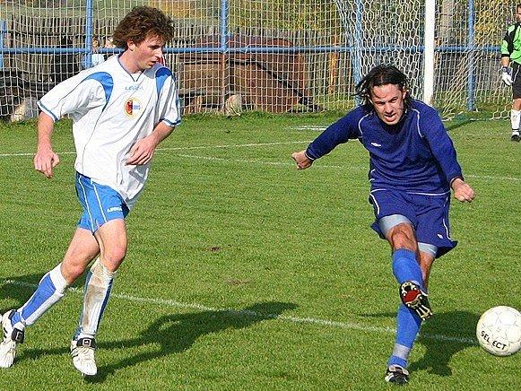 velvarský předstoper Roman Slavíček (vpravo) odkopává míč před hořovickým Nesnídalem. Přihlíží další Velvarák Kopecký.