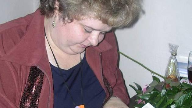 Zdeňka Ortová podepisuje knihu.