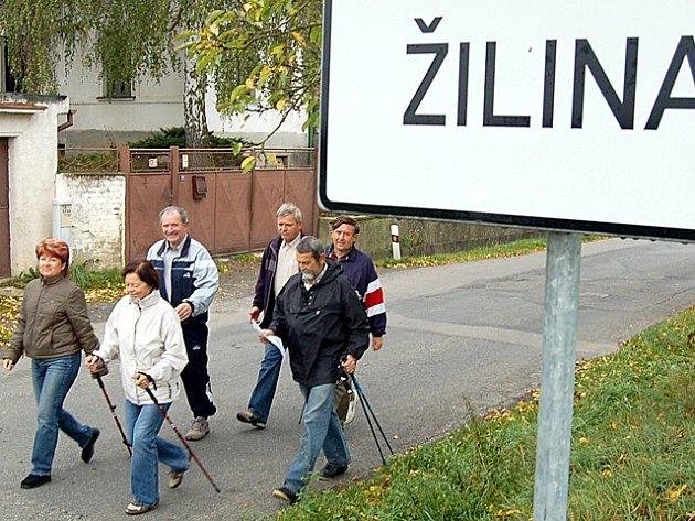ŠLÁPLI DO TOHO. Turisté míjejí ceduli s názvem obce rázným krokem. Několikahodinová trasa je před nimi.