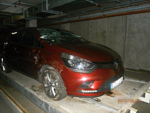 Auto poškozené vparkovacím domě, které se zřítilo vsrpnu zpalety. Škody jsou velké. Poničený sloupek předního okna, střecha, okno, bok auta, lak ipneumatiky.