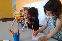 JEDNA ZE SLÁNSKÝCH dobrovolnic při práci s dětmi ve Středisku volného času Ostrov ve Slaném.