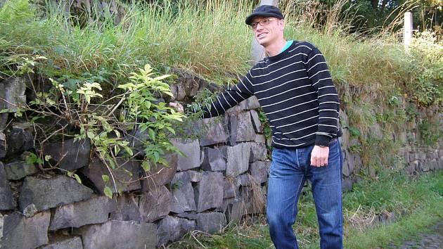 Předseda občanského sdružení Spolek Podprůhon, Vladimír Líba, u jedné ze zdí, která potřebuje opravit.