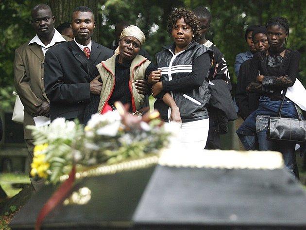 TRUCHLILI. Na pohřbu utonulého Afričana se sešlo několik desítek lidí. V objetí dvou blízkých je žena, která říká, že je Lufilameneho matkou.