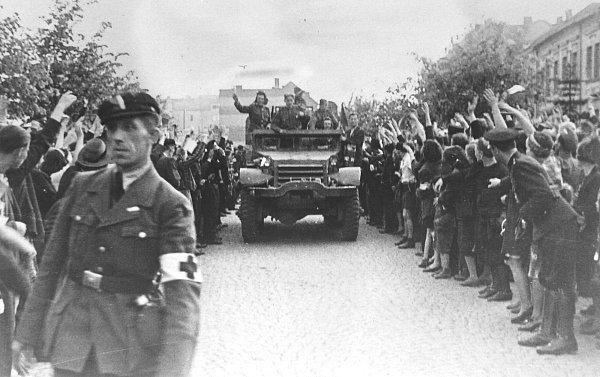 Sovětští vojáci na americkém obrněném transportéru vítaní vulicích Kladna.