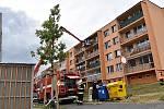 Ve Slaném hoří byt v paneláku, psa hasiči zachránili.