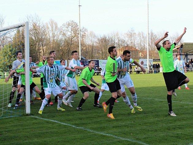 Milan Vošmera (v zelené uprostřed) se právě přikrčil, aby během okamžiku vyskočil a hlavou přesně poslal míč do sítě hostouňského brankáře Pettíka. Díky tomu Velvary vyhrály 1:0.