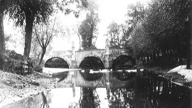 Fotografie z padesátých let minulého století. Před regulací Bakovského potoka protékala voda pod třemi oblouky mostu.