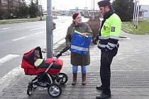POLICISTÉ ROZDÁVALI v ulicích Kladna a Unhoště bezpečnostní reflexní prvky nejen chodcům a cyklistům, ale i řidičům vozidel.