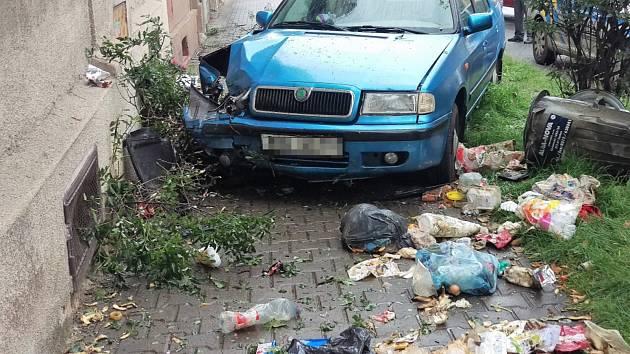 Modrá felicia poté co smetla popelnice a stromek narazila do domu. Auto řídila dvacetiletá šoférka.