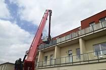 Slánští hasiči použili výsuvnou plošinu, aby osvobodili ženu z balkonu ve třetím patře.