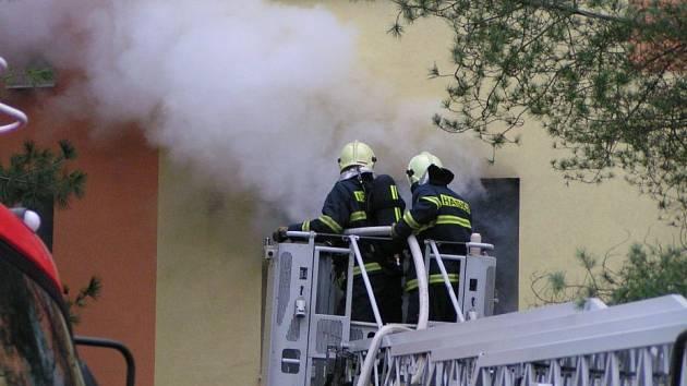 Kladenští hasiči likvidují požár v bytě.
