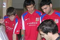 Kluci z týmu Sazená  A –  Pepa Kučera (zleva), Vojta Kovač a Zdeněk Dunko, si prohlížejí tabulku rozdělení jednotlivých her, kterou vyplňuje organizátor turnaje  a ředitel DD Sazená Jiří Beránek.