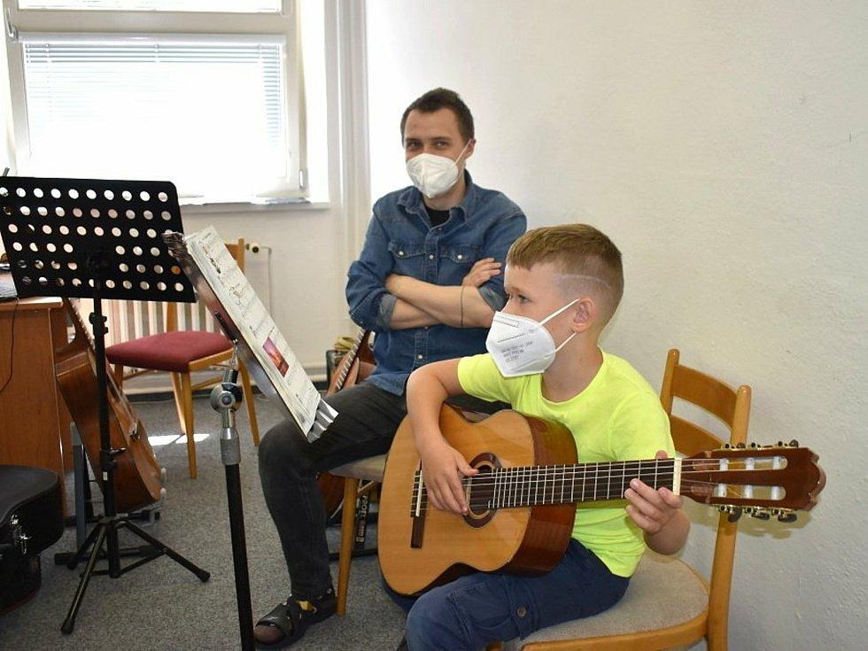 Učitel hry na kytaru Tomáš Frolík se svým žákem.