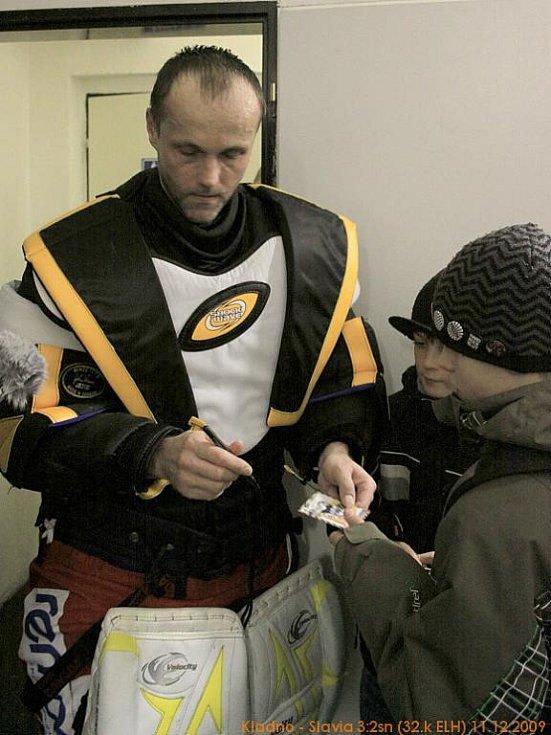 Zdeněk Orct rozdává autogramy na hokejové kartičky.