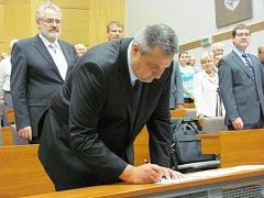Milan Volf potvrzuje svým podpisem slib zastupitele, aby byl vzápětí zvolen staronovým primátorem Kladna.
