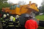 Jeřáb sjel v Kladně z cesty a narazil do parovodu, pomáhat museli hasiči.