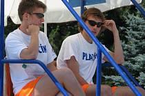 Plavčíci, kteří slouží na bazénech, koupalištích a ostatních vodních plochách, jsou oblečeni do oranžových šortek a bílého trička.