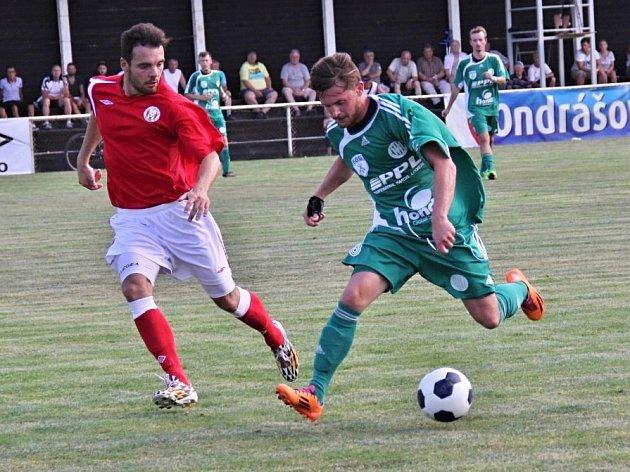 Tuchlovická premiéra v kraji, derby však ovládla Hostouň (v zeleném). jeden z nejlepších hráčů duelu Novák (vpravo) jde přes Pilaře.