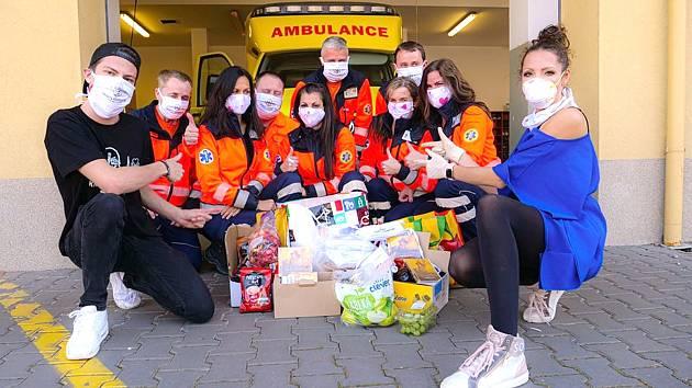 Zpěvačka Olga Lounová (vpravo) a šéf nadace Knight Foundation Adam Soukup (vlevo) předali členům kladenské záchranky ochranné roušky.