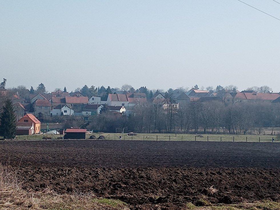 Tam už ne! Pohled z Hostouně na Dobrovíz, kam od 1. 3. 2021 lidé nesmí jít. Obě obce jsou v jiných okresech.