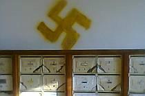 Hákové kříže a znaky SS někdo namaloval nad poštovní schránky a do výtahů.