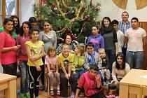 ROMAN PEJŠA (horní řada druhý zprava) s dětmi a kolegyněmi u vánočního stromku v domově v Ledcích.