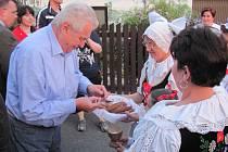 """PREZIDENTA MILOŠE ZEMANA přivítaly u lánské sokolovny místní baráčnice chlebem a solí. """"Máte opravdu moc dobrý chléb,"""" pochvaloval si prezident poté, co symbolicky ochutnal."""
