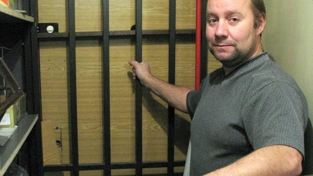 Spolumajitel Petr Přenosil ukazuje dveře a mříž do sklepa, kterými pachatel do obchodu v ulici V. Rabase v Kladně vnikl. Uvnitř pak odcizil cigarety, cukrovinky a finanční hotovost.