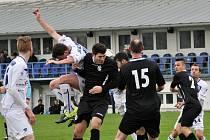 Filip Suchý (uprostřed v bílém) hlavičkuje, v tom hrozil Měcholupům opravdu vážně  a dal i gól.