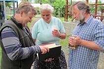 STAROSTA JOSEF KOZEL (vlevo) a manželé Jana a Jaroslav Gűnterovi si prohlížejí pamětní knihu dnes již neexistujícího místního sboru dobrovolných hasičů z roku 1918 a matriku členů, kterou obec dostala od jednoho z účastníků setkání.
