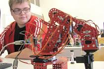 Student čtvrtého ročníku maturitního oboru elektromechanik-technik, osmnáctiletý Filip Vítek ze Hřebče, v nových dílnách dubské střední odborné školy a učiliště ovládá mechanickou ruku prostřednictvím speciálního programu.