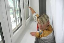 Paní Mirka se marně snaží alespoň dotknout kličky od okna