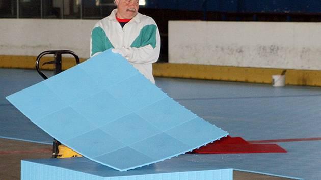 Pokládání povrchu pro in-line hokej na druhé ploše kladenského zimního stadionu.