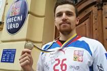 Tomáš Sýkora s medailí z MS před budovou svárovského obecního úřadu.