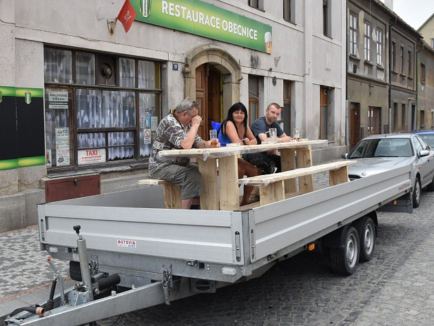 Aktivisté v Unhošti si přitáhli před restauraci valník. Na něm si vychutnávají pivo a cigaretu.