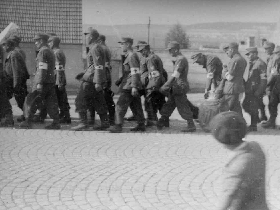 K západním spojencům ustupující kolona poražené a odzbrojené německé armády s sebou nese i své těžce zraněné a mrtvé. Snímek byl pořízen v květnu 1945 v Doksech na karlovarské silnici.