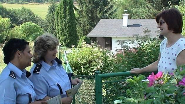 Policistky hovoří s majitelkou rekreační nemovitosti.
