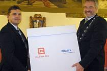 Primátor Kladna Dan Jiránek převzal úsporné žárovky od ředitele prodeje energetické skupiny Romana Kronuse (vlevo).