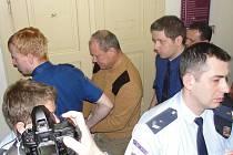 Aktoivista Jiří Fiala (v oranžovém svetru) do soudní síně chodil v doprovodu eskorty.
