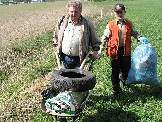 Kolečko plně naložené odpady odváží vedoucí Záchranné stanice AVES Petr Starý (vlevo) z pole u lesoparku Bažantnice.