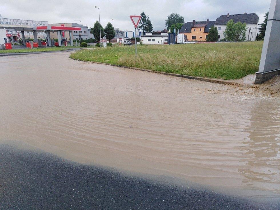 Zaplavená ulice v Klatovech u firmy Lorenc a Benziny ve směru na Luby. Voda teče proudem z pole.