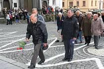 Bývalý MěNV v Klatovech pokládá na oslavách osvobození květiny k pamětní desce, zatímco v pozadí čekají bývalí političtí vězni.